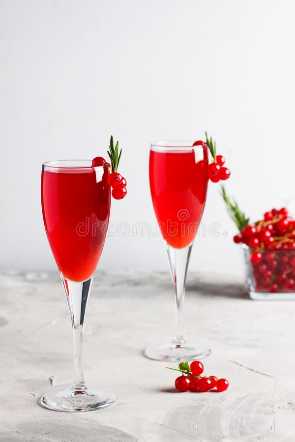 Två exponeringsglas fruktsaft för redcurrantvindrink dekorerade med rosmarin arkivfoton
