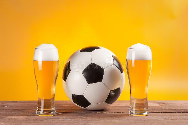 Två exponeringsglas med öl och fotbollbollen nära tvfjärrkontrollen arkivfoto