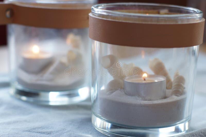 Två exponeringsglas med brinnande stearinljus på tabellen, försiktigt blå gamma royaltyfri bild