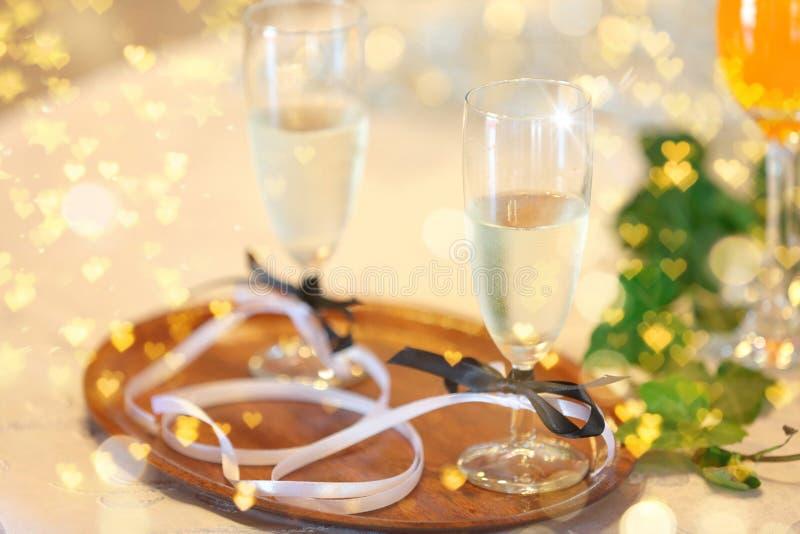Två exponeringsglas med champagne för unga par på ett gifta sig parti fotografering för bildbyråer