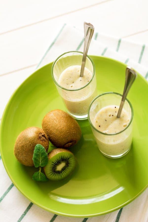 Två exponeringsglas med den nya kiwier och banansmoothien dekorerade mintkaramellsidor fotografering för bildbyråer