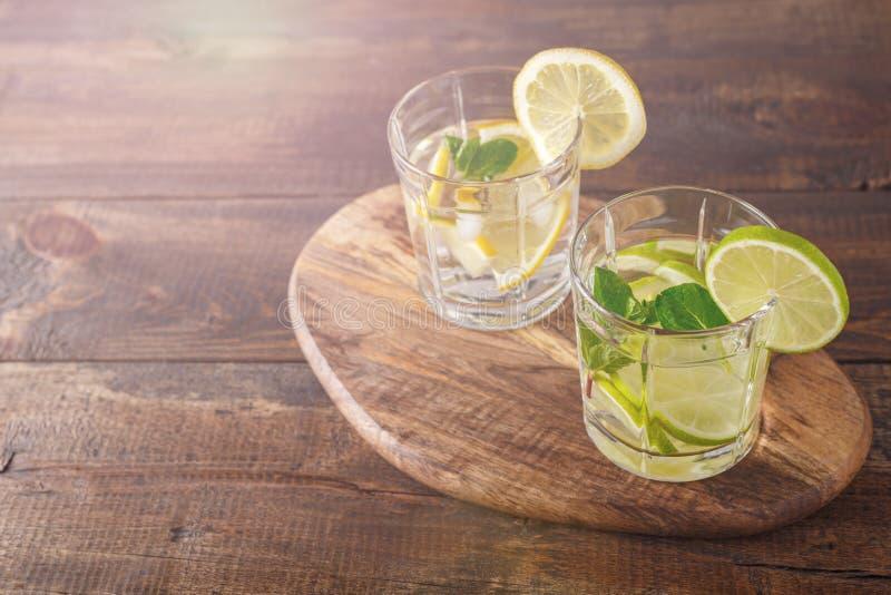 Två exponeringsglas med en sommarcoctail av citronen, limefrukt, mintkaramellen och is på ett träbräde med en kopia av utrymmet arkivfoto