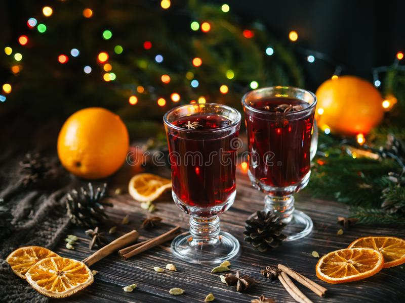 Två exponeringsglas med funderat vin på en trätabell med apelsinen, kanel, kardemumma, anisstjärnor Varm traditionell vinter arkivfoton