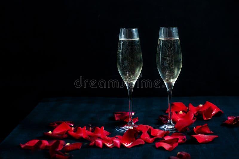 Två exponeringsglas med vita champagne och kronblad av röda rosor på den svarta bakgrunden royaltyfri bild