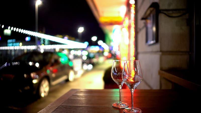 Två exponeringsglas på tabellen i gatakafét, romantisk afton, spontan bekant royaltyfri fotografi