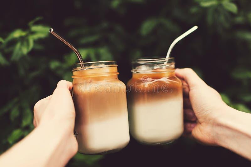 Två exponeringsglaskrus av iskaffe i kvinna- och manhänder royaltyfria bilder