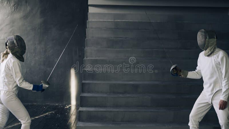 Två fäktare man och kvinna har fäktningmatchen inomhus royaltyfri foto