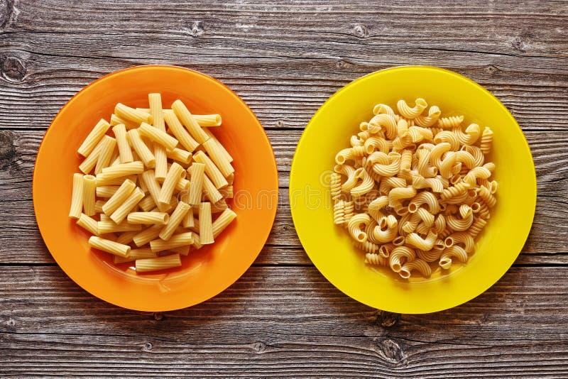 Två färgplattor med pasta på en träbakgrund royaltyfria bilder