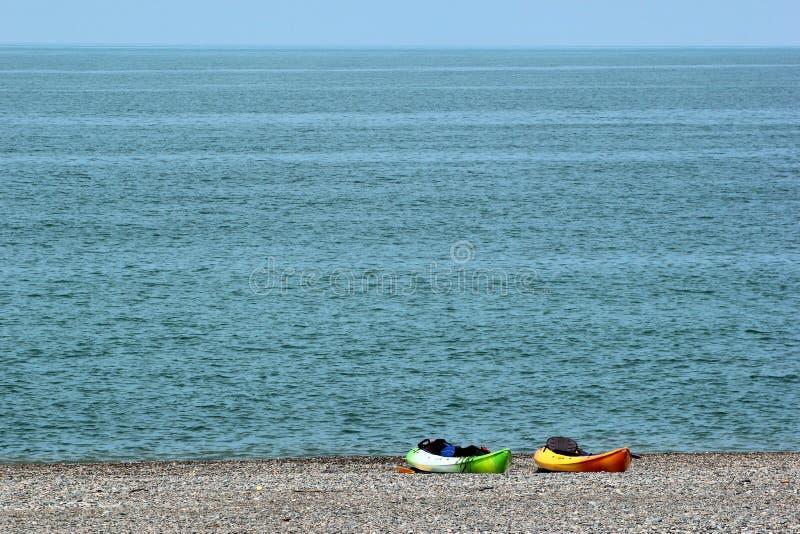 Två färgrika havskajaker med skovlar och flytvästar på den steniga stranden royaltyfri foto