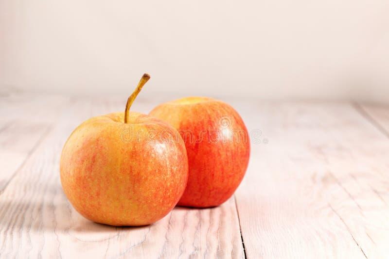 Två färska röda äpplen läggs ner på bondplattor av trä, vega food Färskt äpple, gult, moget royaltyfria foton