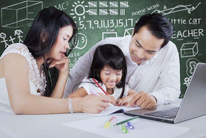 Två föräldrar och deras barn som gör läxa royaltyfri foto
