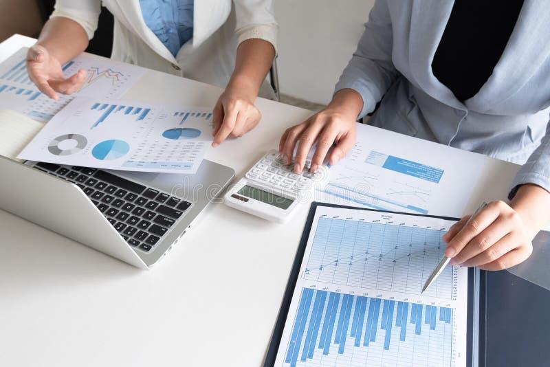 Två företagsledarekvinnor som diskuterar diagrammen och graferna som visar resultaten arkivbild