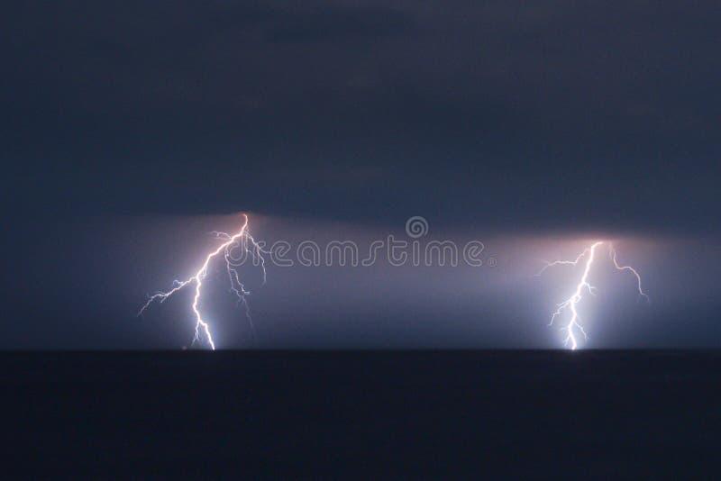 Två förgrena sig blixtslag över Adriatiskt havet nära kusten av Kroatien arkivbild