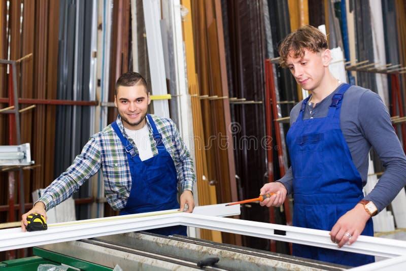 Två försiktiga arbetare som kontrollerar fönster arkivbilder
