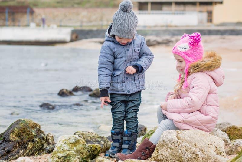 Två förskolebarn som spelar aktivt på den steniga stranden arkivfoton