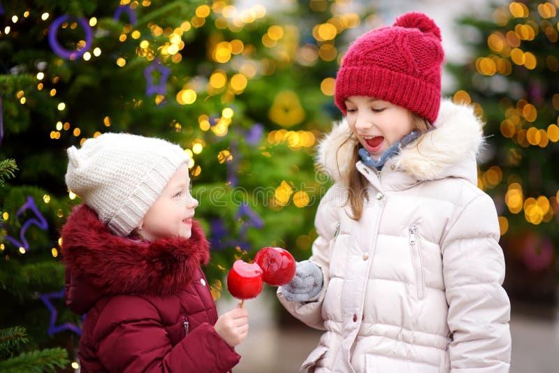 Två förtjusande lilla systrar som äter röda äpplen som täckas med sockerisläggning på traditionell jul, marknadsför arkivbilder