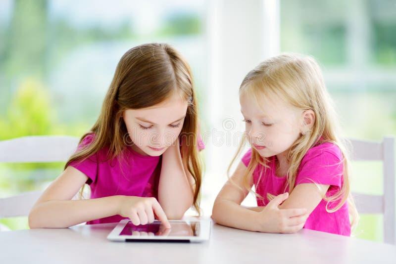 Två förtjusande lilla systrar som spelar med en hemmastadd digital minnestavla Barn i en grundskola arkivfoto