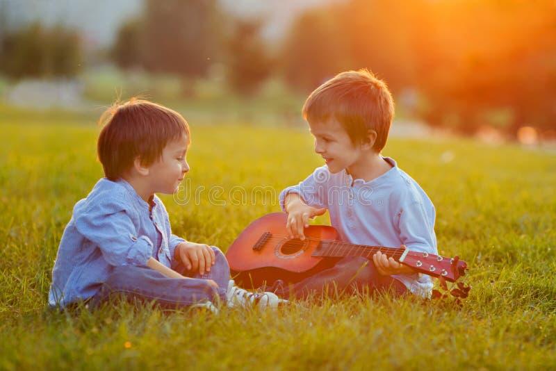 Två förtjusande pojkar och att sitta på gräset som spelar gitarren arkivfoton