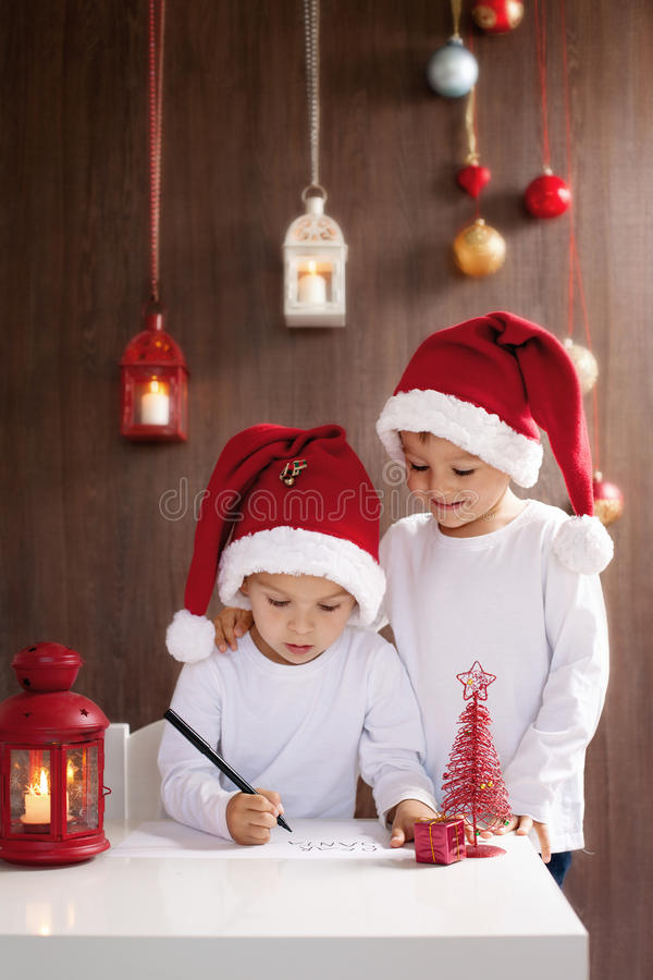 Två förtjusande pojkar som skrivar brevet till jultomten royaltyfri bild