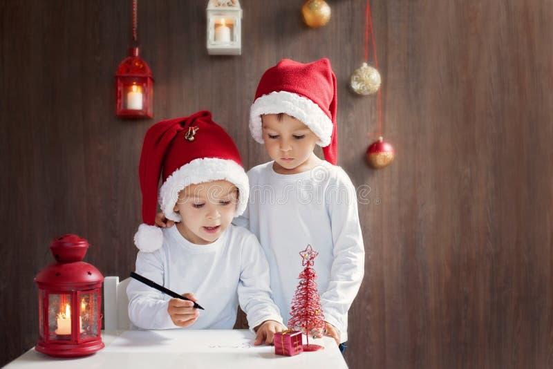 Två förtjusande pojkar som skrivar brevet till jultomten arkivbild