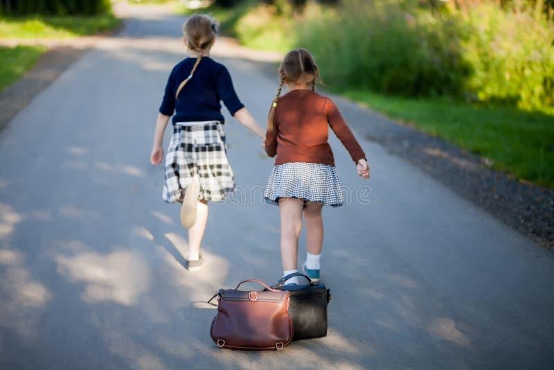Två förtjusande små flickor som hem kör från skola fotografering för bildbyråer