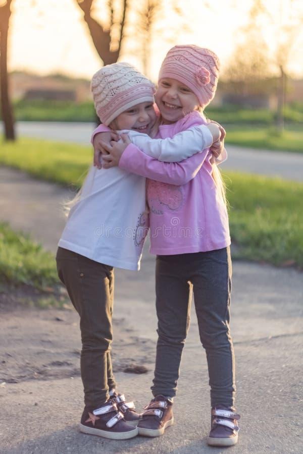Två förtjusande tvilling- lilla systrar som skrattar och kramar sig royaltyfria foton