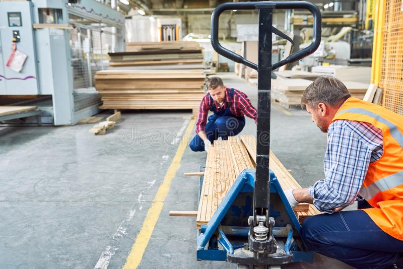 Två fabriksarbetare som flyttar material arkivbilder
