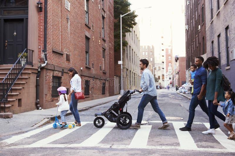 Två familjer med döttrar som korsar vägen fotografering för bildbyråer