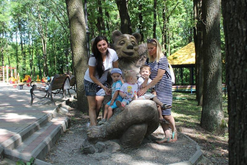 Två familjer med tre barn Mödrar och syskonungar som har rolig det fria i trädgård arkivbild