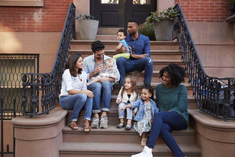 Två familjer med ungar som sitter på framdel, luta sig ner arkivfoto