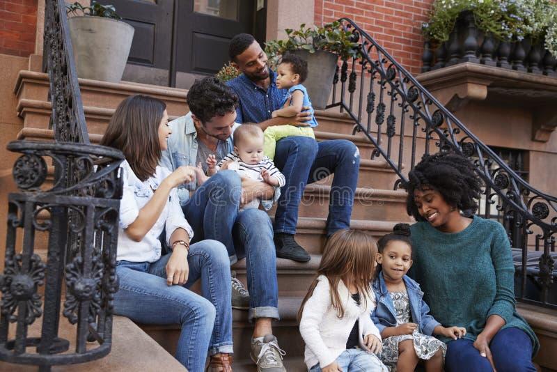 Två familjer med ungar som sitter på framdel, luta sig ner arkivfoton