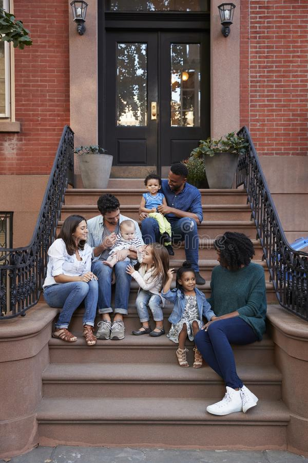 Två familjer med ungar som sitter på framdel, luta sig ner, lodlinjen royaltyfria foton
