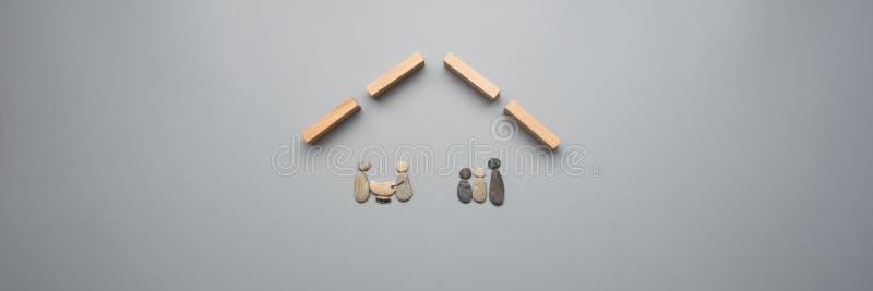 Två familjer som göras av kiselstenar under ett tak som göras av träpinnor arkivbilder