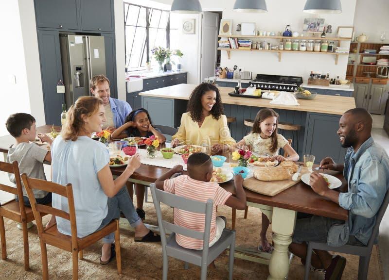 Två familjer som har hemmastadd lunch tillsammans, högstämd sikt arkivfoto