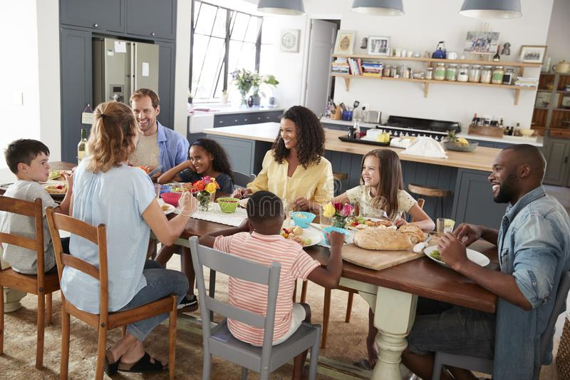 Två familjer som har hemmastadd lunch tillsammans, högstämd sikt royaltyfri bild
