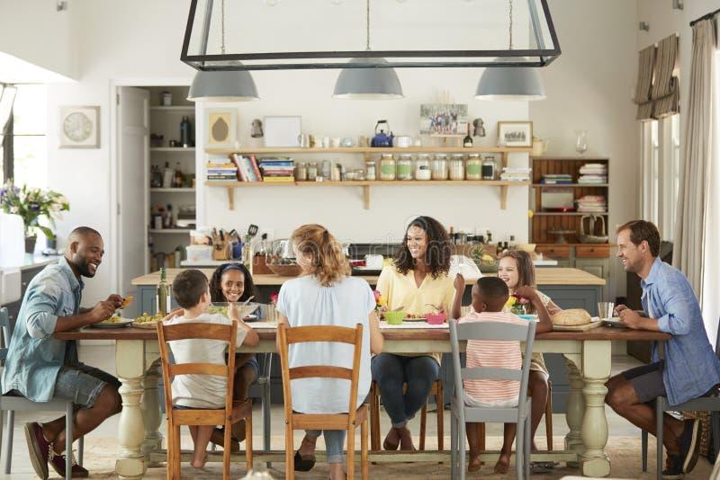 Två familjer som har lunch tillsammans i köket hemma royaltyfri foto