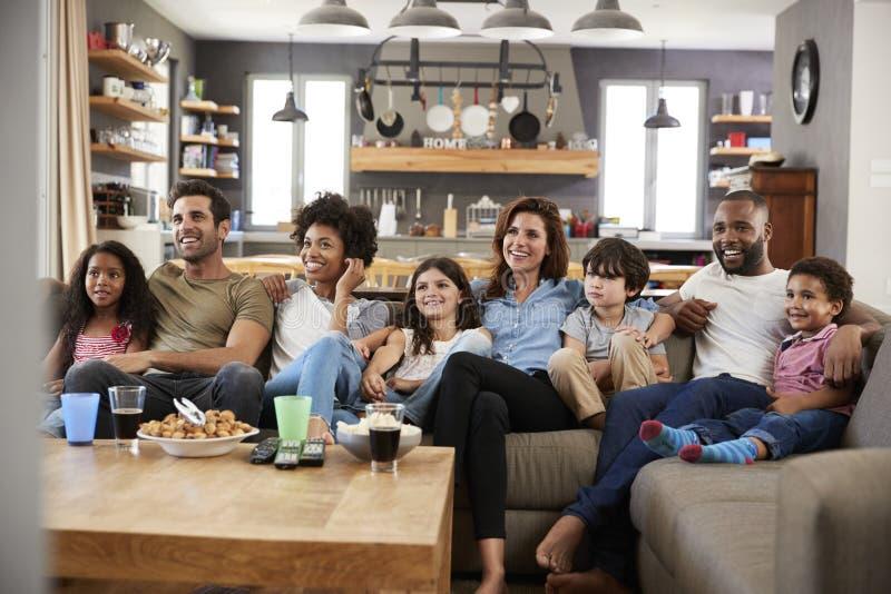 Två familjer som sitter på Sofa Watching Television Together arkivfoton