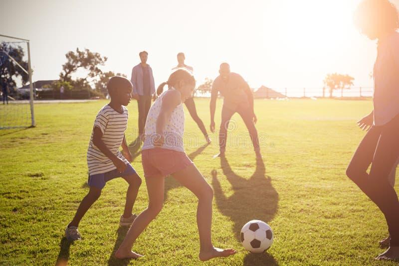 Två familjer som spelar fotboll i en parkera arkivbild