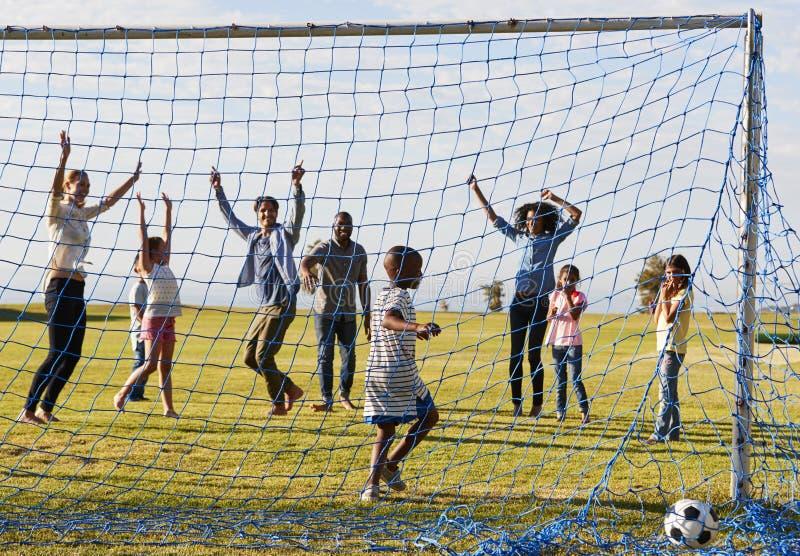 Två familjer som spelar fotboll parkerar in, att fira ett mål arkivfoton