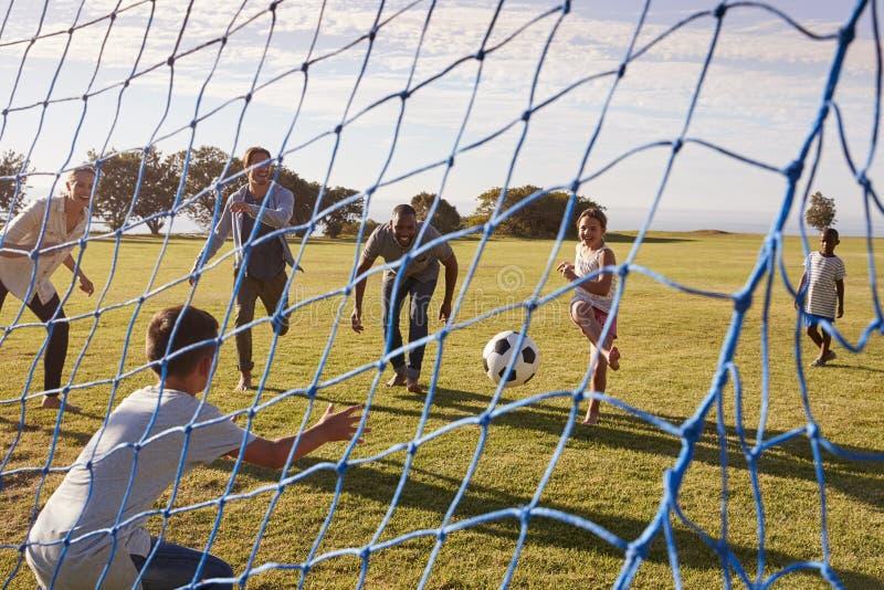 Två familjer som spelar fotboll parkerar in, sett igenom mål netto royaltyfria foton