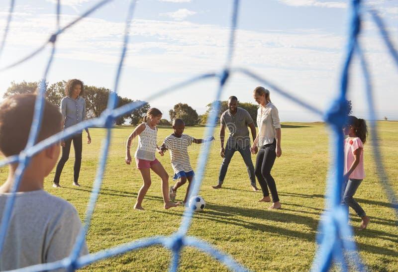 Två familjer som spelar fotboll parkerar in, sett igenom mål netto arkivfoto