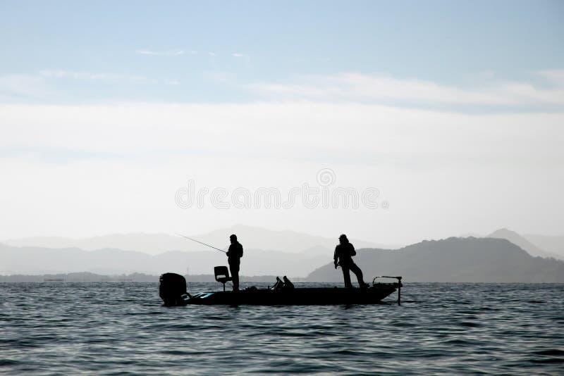 Två fiskare fiskar på en båt i Japan's sjö arkivbild