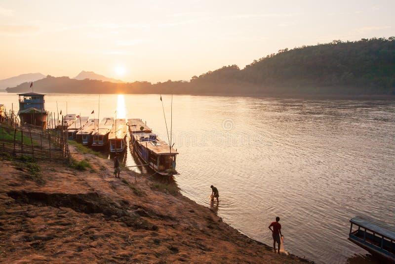 Två fiskare med fisknät i Mekonget River på solnedgången S arkivbild