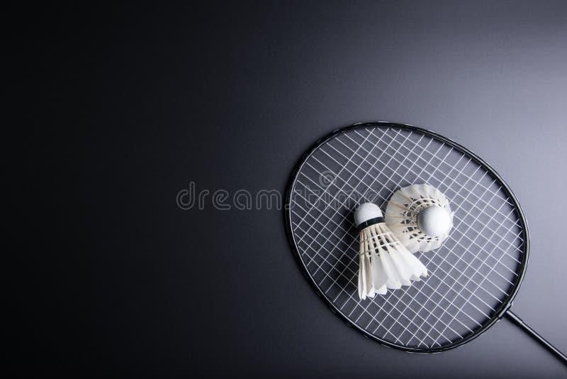 Två fjäderbollar och badmintonracket på svart bakgrund sport royaltyfria foton