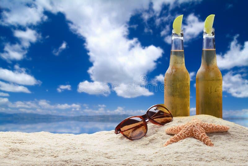 Två flaskor av öl med limefrukt på stranden. royaltyfria bilder