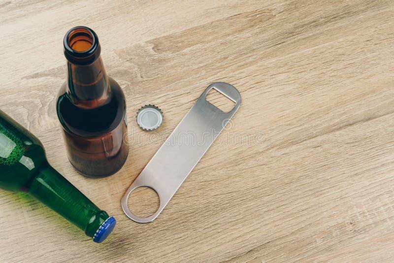 Två flaskor av öl och en rostfritt stålflasköppnare fotografering för bildbyråer