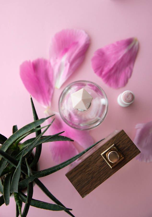 Två flaskor av Junian andar, toalettvatten, den bästa sikten, det rosa locket och en trädflaska med rosa blommakronblad, hemlagad royaltyfria bilder