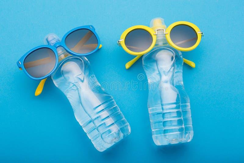 Två flaskor av vatten på en blå bakgrund är liknande till folk som solbadar på stranden, buteljerade exponeringsglas, begreppssom royaltyfri fotografi