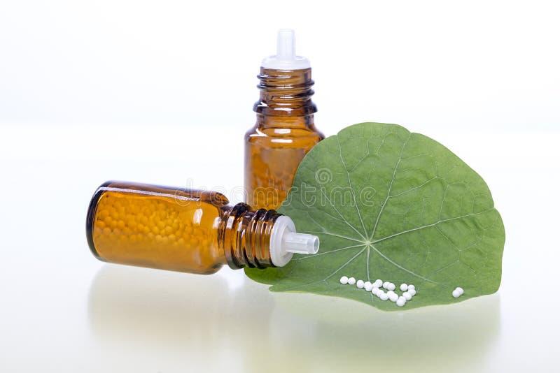 Två flaskor med homeopatismå kulor royaltyfri fotografi