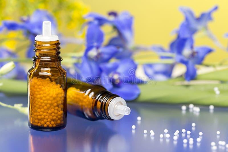 Två flaskor med homeopatismå kulor och blommor arkivbild